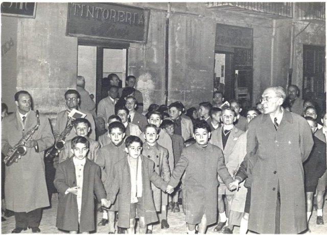 Alcoy, Procesión del Viernes Santo (1955 ó 1956). Fernando de Mora, dirige un grupo de niños cantores acompañados por músicos de la Corporación Musical Primitiva. Foto: Rafael Serra