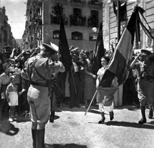 Fotografia de Michele Francone que presenta la exposició. És el lliurament de la bandera que han brodat les joves al 86 Batalló de la 22 brigada Mixta de l'Exèrcit Popular